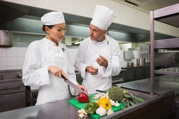 Chef teaching trainee how to slice vegetables