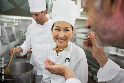 Head chef tasting a spoon of soup