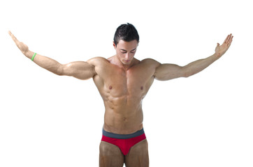 Muscular young bodybuilder looking down with arms spread open