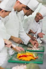 Row of trainee chefs slicing vegetables with tutor watching