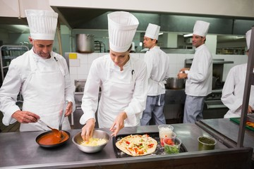 Chefs preparing a pizza together