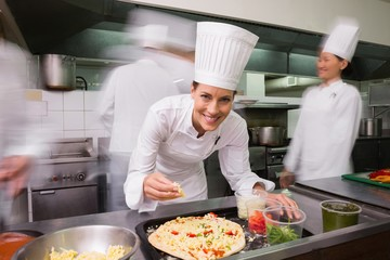Happy chef preparing a pizza