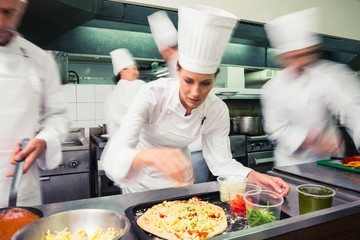 Focused chef preparing a pizza