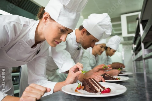 Row of chefs garnishing dessert