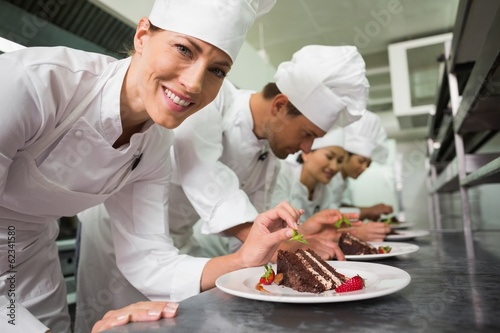 Row of chefs garnishing dessert with one smiling at camera