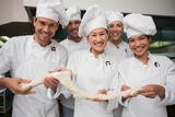 Chefs holding a stretched piece of dough smiling at camera