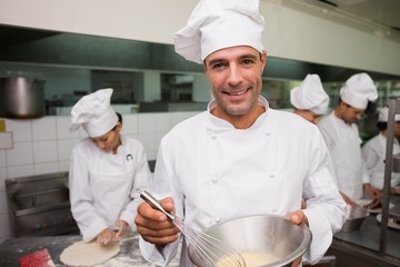 Happy chef whisking bowl of eggs smiling at camera
