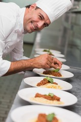 Happy chef putting basil leaf on spaghetti dish