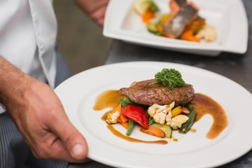 Chef holding steak dinner with vegetables and gravy