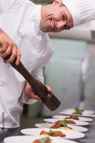 Happy chef grinding pepper over spaghetti dish