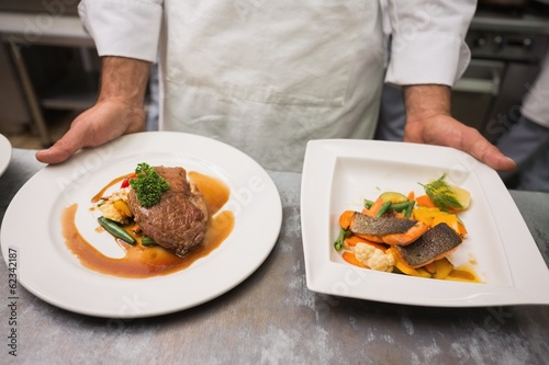 Chef holding steak dinner and salmon dinner