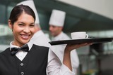 Happy waitress holding tray with coffee cup
