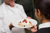 Waitress taking dessert from chef