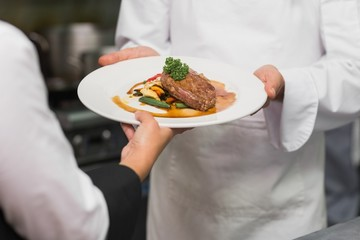 Waitress taking steak dinner from chef