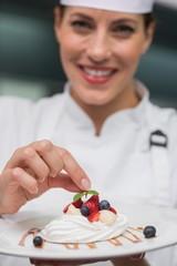 Smiling chef putting mint leaf on meringue dish