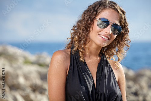 Woman in a black dress on the ocean coast