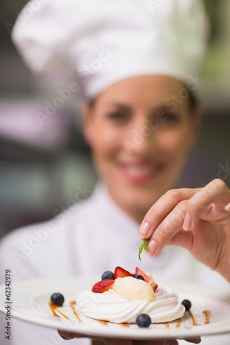 Happy chef smiling at camera holding dessert plate
