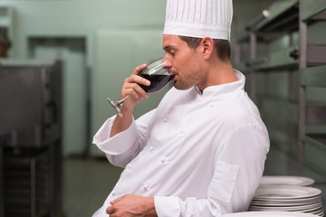 Chef relaxing with glass of red wine after work