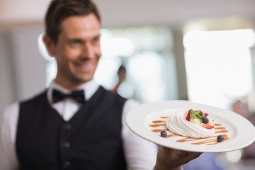 Handsome waiter showing a dessert plate