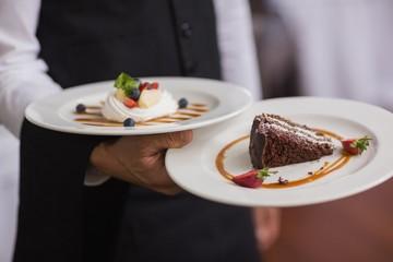 Waiter showing two dessert plates