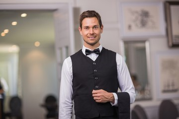 Handsome waiter smiling at camera
