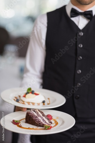 Waiter showing two dessert plates