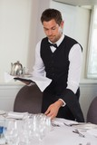Waiter holding tray and setting table