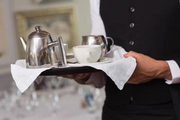 Waiter holding tray with afternoon tea