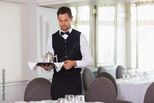 Handsome waiter holding tray and setting table