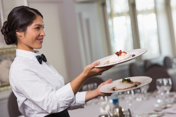 Pretty waitress holding two dessert plates