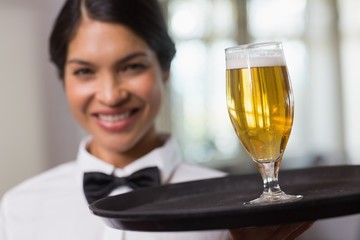 Pretty waitress holding tray with glass of beer