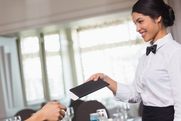 Happy waitress holding the bill