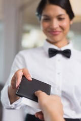 Happy waitress holding the bill
