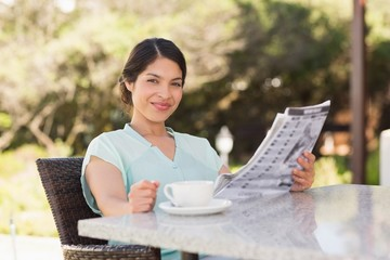 Businesswoman having coffee and reading the paper