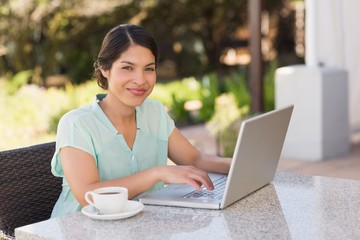 Businesswoman having coffee and working on laptop