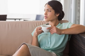 Thoughtful businesswoman having coffee sitting on sofa