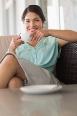 Happy businesswoman having coffee sitting on sofa