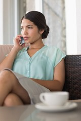 Businesswoman having coffee sitting on sofa on a phone call
