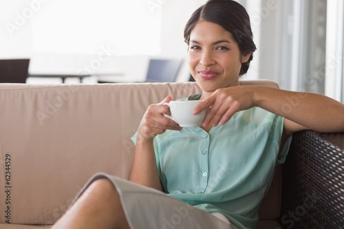 Happy businesswoman having coffee sitting on sofa