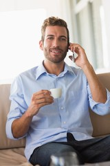 Handsome businessman on a phone call and drinking espresso