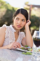 Annoyed woman eating a salad