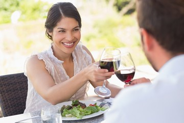 Happy couple toasting with red wine on a date