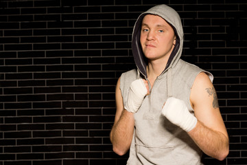 Muscular young boxer with bandaged fists