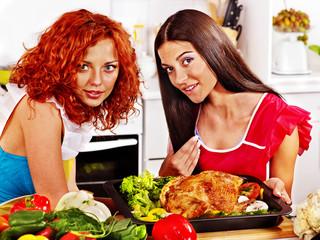 Women cooking chicken at kitchen.