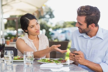 Annoyed woman taking phone from her date
