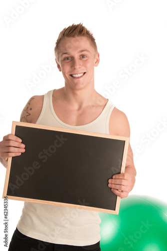 Fit man holding blackboard in gym