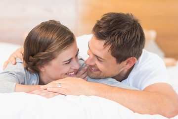 Happy couple lying on a bed