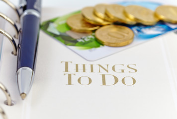 Credit card, golden coins and ball pen on the page of an organiz