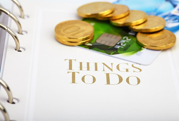 Credit card, golden coins  on the page of an organizer with the