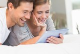 Happy couple on bed using tablet pc
